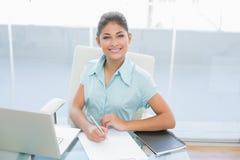 Onderneemster met laptop het schrijven document in bureau Stock Fotografie