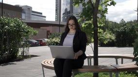 Onderneemster met laptop op bank stock videobeelden