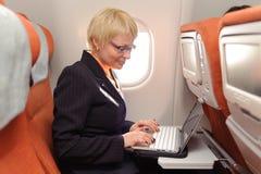Onderneemster met laptop op de raad van vliegtuig stock foto's