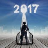 Onderneemster met nummer 2017 en roltrap Stock Afbeeldingen