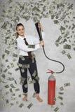 Onderneemster onder een regen van geld van een brandblusapparaat stock afbeelding