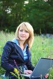 Onderneemster op gras met laptop royalty-vrije stock afbeeldingen