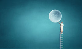 Onderneemster op ladder die maan bereiken Royalty-vrije Stock Fotografie