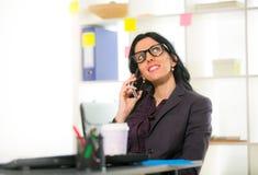 Onderneemster op telefoon in haar bureau Stock Afbeeldingen