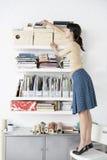 Onderneemster Reaching For Shelf in Huisbureau royalty-vrije stock foto