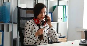 Onderneemster in rode hoofdtelefoons die creditcard houden en op smartphone spreken stock videobeelden
