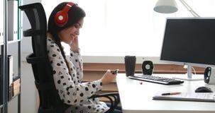 Onderneemster in rode hoofdtelefoons die smartphone in modern bureau gebruiken stock videobeelden