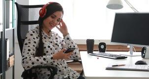 Onderneemster in rode hoofdtelefoons die smartphone in modern bureau gebruiken stock video