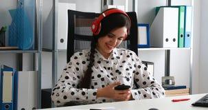 Onderneemster in rode hoofdtelefoons die smartphone in modern bureau gebruiken stock footage