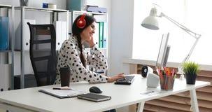 Onderneemster in rode hoofdtelefoons het luisteren muziek en het gebruiken van laptop stock footage