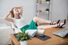 Onderneemster rustende het ontspannen benen op de lijsthanden achter haar hoofd en het zitten van een stoel in bureau stock afbeeldingen