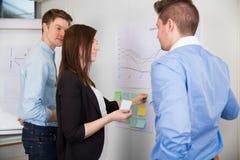 Onderneemster Sticking Adhesive Notes terwijl Status door Colleagu stock foto's