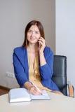 Onderneemster in vrijetijdskleding die mobiel telefoongesprek neemt en nota's schrijft in kalender bij bureau Royalty-vrije Stock Foto