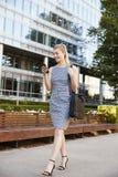 Onderneemster Walking To Work in Stad die Mobiele Telefoon bekijken stock afbeelding