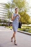 Onderneemster Walking To Work in Stad die Mobiele Telefoon bekijken royalty-vrije stock afbeelding