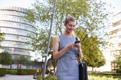 Onderneemster Walking To Work in Stad die Mobiele Telefoon bekijken royalty-vrije stock afbeeldingen