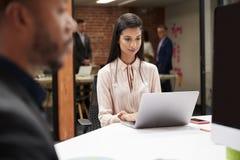 Onderneemster Working At Desk op Laptop in Open Planbureau met Collega's op Achtergrond stock fotografie