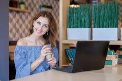 Onderneemster Working On Laptop in Koffiewinkel De jonge bedrijfsvrouw gebruikt laptop in koffie Onderneemster het werk het typen Royalty-vrije Stock Foto's
