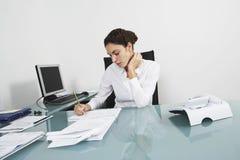 Onderneemster Writing On Document bij Bureau stock afbeeldingen