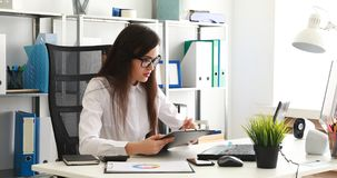Onderneemster in zwarte glazen die documenten vullen en aan laptop in modern bureau werken stock videobeelden