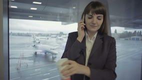 Onderneemsterbesprekingen op de telefoon in de luchthavenzaal dichtbij venster stock video