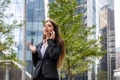Onderneemsterbesprekingen op mobiele telefoon voor moderne bureaugebouwen royalty-vrije stock afbeelding