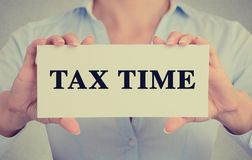 Onderneemsterhanden die kaartteken met het bericht van de belastingstijd houden Stock Afbeelding