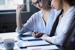 Onderneemsters die nieuw businessplan samen bespreken Stock Foto