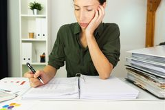 Onderneemsters die op een lijst en het berekenen verkoopresultaten zitten stock foto
