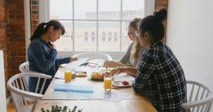 Onderneemsters die over documenten bespreken terwijl het hebben van ontbijt 4k stock video