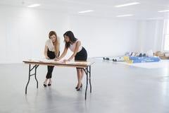 Onderneemsters die plannen voor bureau binnenlands ontwerp bespreken stock fotografie
