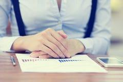 Onderneemsterzitting bij lijst voor financieel document Stock Foto