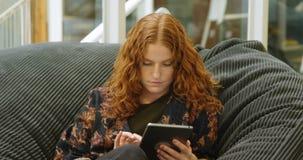 Onderneemsterzitting op de leunstoel en het gebruiken van digitale tablet 4k stock footage