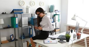 Onderneemsterzitting op witte lijst en het gebruiken van smartphone in modern bureau stock footage
