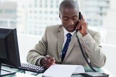 Ondernemer die een telefoongesprek maakt terwijl het lezen van een document Stock Afbeeldingen