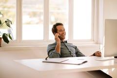 Ondernemer die op mobiele telefoon spreken terwijl het werken aan computer a stock fotografie