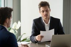 Ondernemer die overeenkomstenvoorwaarden in bureau bestuderen stock afbeeldingen