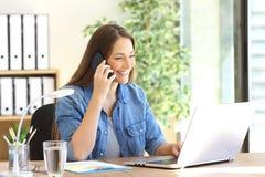 Ondernemer die telefoon uitnodigen die met laptop werken stock fotografie