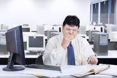 Ondernemer die terwijl het bijten van hamburger werken stock afbeelding