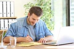 Ondernemer het schrijven adres in een opgevulde envelop stock afbeeldingen