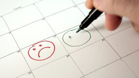 Onderteken de dag in de kalender met een pen, trek een glimlach