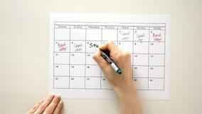 Onderteken de dag in de kalender met een pen, trek een goede slechte dag stock videobeelden