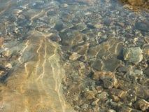 Onderwaterbezinningen over de overzeese kiezelstenen Stock Fotografie