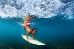 Onderwaterfoto van surfermeisje op brandingsraad in oceaan Stock Afbeeldingen