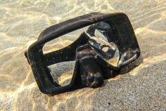Onderwaterfoto - zon die aan rubber zwart het duiken masker op zand in ondiep water glanzen stock afbeelding