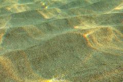 Onderwaterfoto - zon die op zand glanzen stock afbeeldingen