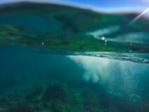 Onderwaterlandschap met natuurlijke waterspleet, blauwe hemel hierboven en groen hieronder water royalty-vrije stock afbeelding