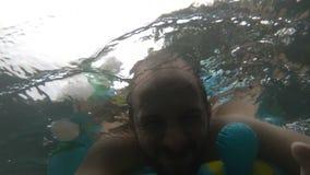 Onderwaterportret van de glimlachende mens Persoon die pret in zwembad hebben De vakantieconcept van de zomer selphi stock footage
