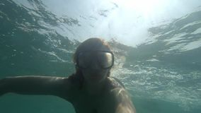 Onderwaterselfie die van jonge vrouw in overzees of oceaan blauw water met zwemmend masker zonder aqualong met zon snorkelen stock videobeelden