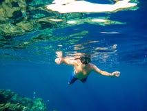 Onderwaterspruit van een jonge jongen die in rode overzees snorkelen Royalty-vrije Stock Foto's